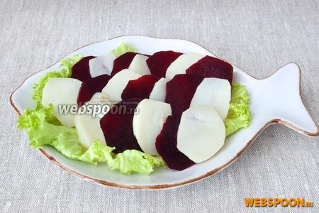 На блюдо выложить листья салата, затем внахлёст и чередуя, выложить ломтики картофеля и свёклы.