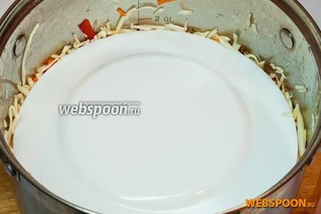 Залейте холодным маринадом и перемешайте. Капусту следует прижать чем-то тяжёлым — для этого можно накрыть её тарелкой и поставить сверху банку с крупой или ступку (всё что подходит вам по весу и размеру).