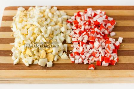 Сваренные вкрутую яйца чистим и нарезаем небольшими кубиками. Также нарезаем крабовые палочки.