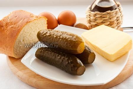 Для приготовления салата вам понадобятся: полутвёрдый сыр, маринованные огурцы, яйца, чеснок, батон, майонез и масло для жарки.