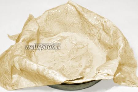 Просторную форму (у меня 26х6 см) смазать маслом и выстелить одним листом лаваша. Если лаваш очень большой, можно часть его оторвать, но края должны свисать за пределы формы. Промазать весь лаваш, включая свисающие края, приготовленным соусом.
