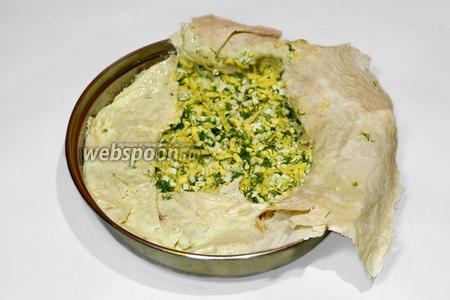Выложить начинку из сыра, яиц и укропа, накрыть краями нижнего лаваша, также дополнив кусочками незакрытые места.