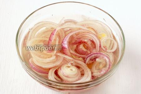 Лук нарезать тонкими кольцами. Залить 150 мл кипятка, добавить уксус. Выдержать лук в маринаде 5 минут.