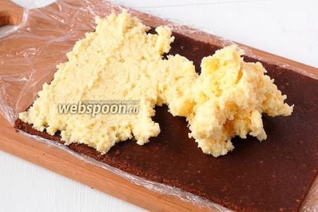 Снять верхнюю плёнку. Подровнять шоколадное тесто, чтобы вышел прямоугольник. Сверху выложить кокосовый крем. Разровнять.