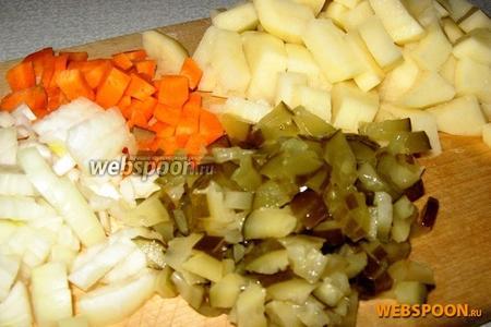 Туда же опускаем нарезанный кубиками картофель.   Мелко режем лук и морковь для заправки. Солёные огурчики тоже режем на мелкими кусочками.