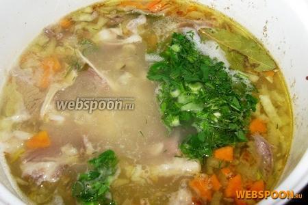 Когда картофель в рассольнике станет мягким, добавляем овощную заправку. Доводим до кипения, для запаха добавляем 2 лавровых листа, кипятим на медленном огне ещё 5-6 минут. Если кислоты маловато — добавляем по вкусу рассол. Вводим в суп мелко порезанную зелень, закрываем крышкой и снимаем с огня. Даём настояться. Подаем со сметаной и свежей зеленью.