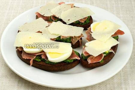Уложить на бутерброды яйцо и несколько пластинок сыра пармезан.