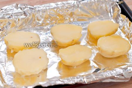 Картошку достаем, остужаем, чистим и режем на половинки. У каждой половинки срезаем кусочек донышка, чтобы «лодочка» могла стоять. Выкладываем «лодочки» на застеленный фольгой противень.