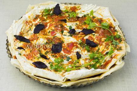 Завершающий, третий слой лаваша также смазать томатным соусом и творогом. Края смазать оливковым маслом. Украсить зеленью.