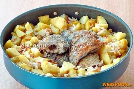 В середину огнеупорной формы выложить обжаренных карасей, по кругу разложить картофель, и посыпать всё жареным луком.