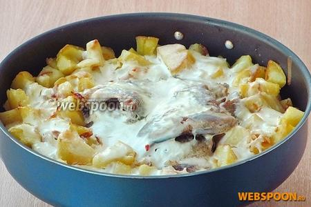 Сметану развести водой, посолить и полить этой смесью выложенные картофель и рыбу.