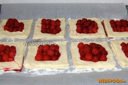 В «окошечки» аккуратно выложить ягоды. Сделать это желательно в виде небольшой горки, потому что тесто в процессе приготовления поднимется, а ягоды осядут, и таким образом будет достигнут приблизительно одинаковый уровень начинки и теста.