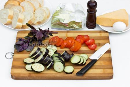 Нарежем тонкими ломтиками баклажан и помидоры.