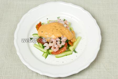 На овощи выложить креветки, полить салат соусом, ещё раз поперчить и в таком виде подавать.