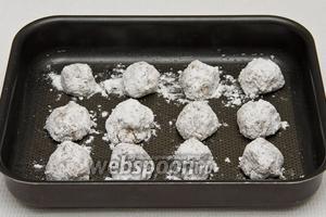 Из смеси сахара, белков и арахиса формируем шарики, обмакиваем их в пудре и выкладываем на смазанный подсолнечным маслом противень. Ставим шарики в духовку на 15 минут при температуре 180°C.