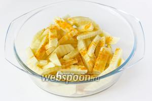 Перекладываем картофельные «палочки» в миску, посыпаем куркумой и вливаем оливковое масло. Тщательно перемешиваем.