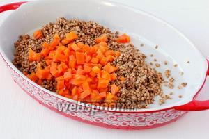 В форму для запекания выложить подготовленную крупу, добавить варёную морковь, порезанную кубиками.