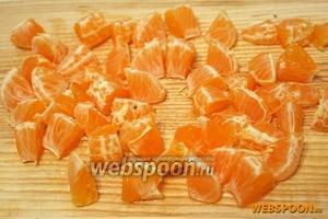 С мандарин очистите кожуру, разделите их на дольки и порежьте каждую дольку на несколько частей.