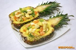 Салат выложите в половинки ананасов, украсьте и подавайте.