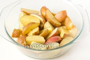 Складываем картофельные ломтики в ёмкость, поливаем оливковым маслом и хорошенько руками перемешиваем, чтобы каждый ломтик был покрыт тонким слоем масла.