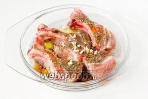 Свиные рёбра складываем в миску, поливаем бальзамическим уксусом, оливковым маслом, посыпаем солью, чёрным молотым перцем, сухим базиликом и измельчённым чесноком.