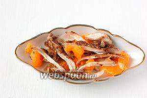 На дно порционного салатника уложить запечённое мясо и мандарины.