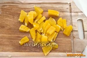Порезать апельсин на небольшие кусочки.