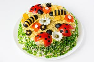Теперь, ориентируясь по фотографии, собираем и выкладываем на салат «пчёлок» — 2 шт., «божьих коровок» — 3 шт., «цветы».