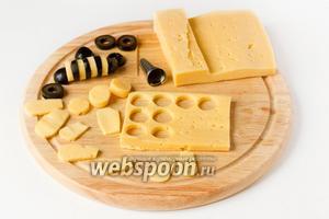 Теперь подготовим материал для нашей «поляны». Займёмся «пчёлками». Маслины нарезаем на кольца, из 1 шт. маслины получится 4 колечка, всего таким образом разрезаем 4 маслины для 2 пчёл (края нам не все понадобятся). Из сыра вырезаем тонкий пласт (по толщине примерно одинаковый с толщиной колец маслин). Формочкой (у меня насадка на кондитерский мешок) вырезаем из сыра кольца. Они должны получиться примерно такими, как и кольца из маслин. Также из сыра вырезаем «крылья» — всего 8 шт. Также вырезаем из маслин «головы» пчёлкам — одну маслину разрезаем поперёк на 2 части и каждую ещё вдоль (из 1 маслины получится 4 части, 2 нам понадобятся, а 2 нет).