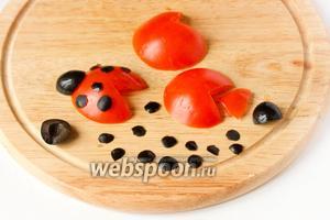Теперь подготовим «божьих коровок». С помидора срезаем одну сторону и вырезаем с одной стороны треугольник — получится «тельце с крыльями». Получается, что у одного помидора мы берём 2 части (2 стороны срезаем), а у ещё одного только одну. Из маслин вырезаем «головы» и пятна на тельце.