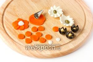 Теперь подготовим «цветы». Из яйца делаем зубчатые цветочки (1 яйцо на 2 цветка) — в центр которых выкладываем каперсы или зелёный горошек (или кусочек моркови), из маслин также вырезаем зубчатые цветы (в центр — кубик сыра), из колец моркови вырезаем насадкой для кондитерского мешка кольца, формируем цветок (3 шт.), в центре которых кружок яичного белка.