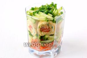 На рулетики — 1 чайную ложку соуса, порезанные тонкой соломкой огурцы, порезанный зелёный лук.