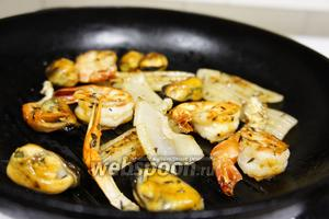 Пора жарить морепродукты! На горячую сковороду влить масло и уложить тимьян, следом уложить хвосты креветок, мидии, кусочки кальмара, клешни рака и хвост. Посолить, изъять тимьян, перевернуть все морепродукты и хорошенько взбрызнуть лимоном. Снять с огня.