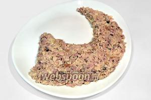 Салат у нас будет слоёным, для его сборки нам нужно большое плоское блюдо овальной или круглой формы. Курицу перемешиваем с луком, укладываем первым слоем в виде рога и слегка смазываем сверху майонезом.