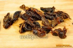 Запарьте чернослив кипятком на 10-15 минут. Обсушите. Нарежьте соломкой.