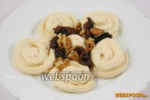 Выложите слой безе на тарелку. Сверху положите чернослив с орехами.