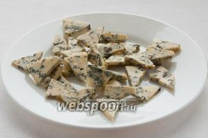 Сыр порежьте на небольшие треугольники.