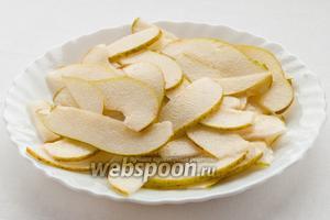 Грушу порежьте на четвертинки, удалите сердцевину и нашинкуйте тонкими ломтиками. Не теряя времени смочите ломтики груши лимонным соком, для того чтобы она не потемнела.