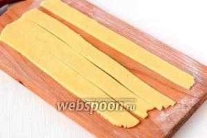 Раскатать тесто толщиной 0,3 см. Нарезать его полосками шириной 2 см и длиной 25 см.