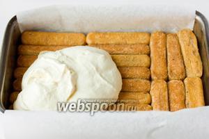 На нижний слой печенья выкладываем половину всего сырного крема.