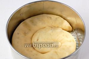 Форму диаметром 18 см смазать растительным маслом и на дно уложить улитку из теста, распределив её по форме.