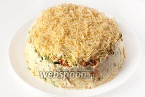 Последний верхний слой — натёртый ранее твёрдый сыр. Бока салата подравниваем лопаткой, хорошенько смазываем майонезом.
