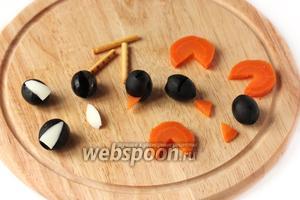 Теперь собираем пингвинов. Для трёх пингвинов нам понадобится 6 маслин без косточек, отваренная морковь (всего было 3, 2 натёрли в салат, и 1 осталась для украшения, вот её-то и берём), соломка, яичный белок (из которого ушки медведю вырезали). Из этих продуктов вырезаем части пингвина, ориентируясь по фотографии (описать сложно, конечно, я думаю, и так понятно).