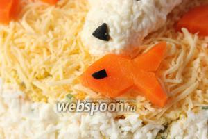 Из кусочка моркови вырезаем рыбку, делаем ей глаз из кусочка маслины, выкладываем рядом с медведем.
