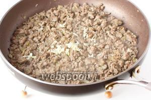 Когда свиной фарш будет готов, добавляем в сковороду измельчённый чеснок, соль и чёрный молотый перец. Перемешиваем и обжариваем ещё около минуты на медленном огне.
