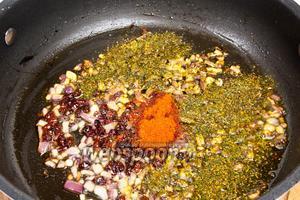 В сковородку добавить столовую ложку масла, вначале обжарить лук до золотистого цвета, а затем добавить остальные специи и обжарить ещё несколько секунд, пока специи не раскроют аромат.