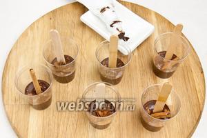 Заполнить каждый стаканчик на 1/3, вставить деревянные палочки и украсить анисом и палочками корицы, а также посыпать молотой корицей.