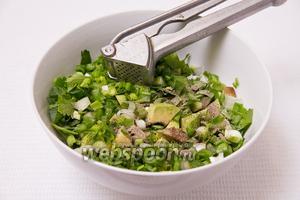 Добавляем в салат один зубчик чеснока, выдавленный через пресс. Также солим, перчим и снова перемешиваем салат.