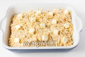 Оставшееся масло (50 г) нарезаем мелкими кубиками и выкладываем на поверхность запеканки.