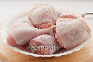 Куриные окорочка промойте под проточной водой и порежьте на порционные куски.